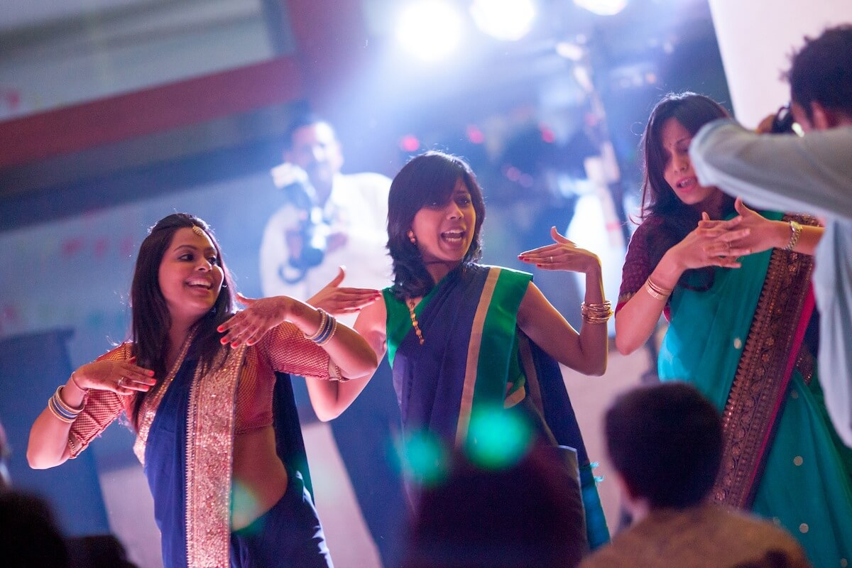 girls dancing at an indian wedding candid photograph